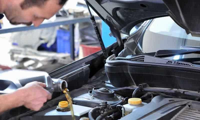 Mecánico agregando aceite al motor